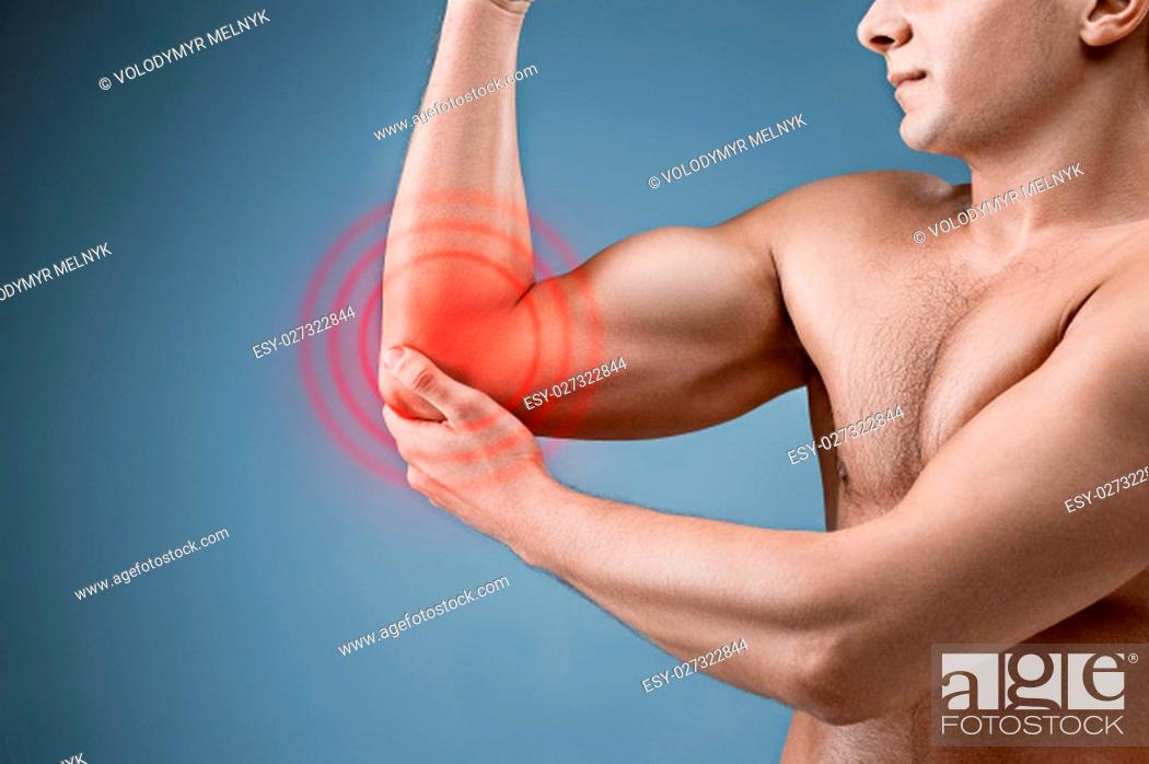 Stock Photo: Man With Pain In Elbow. Pain relief concept on gray studio background.