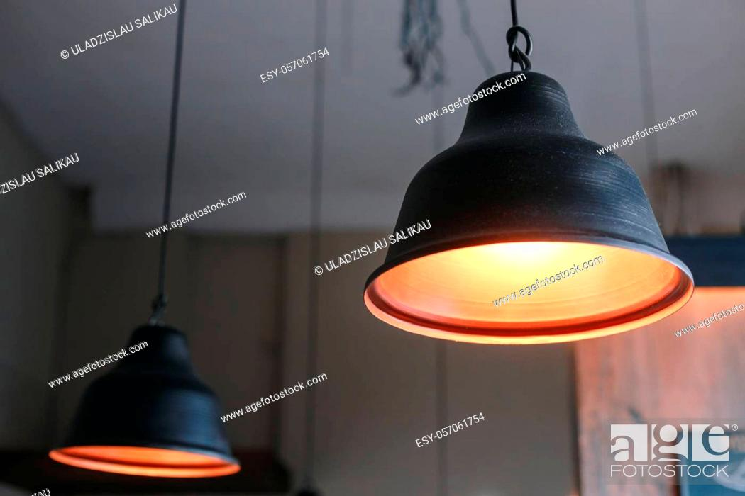Stock Photo: Black metal lamps hanging from the eiling grey wall interior.