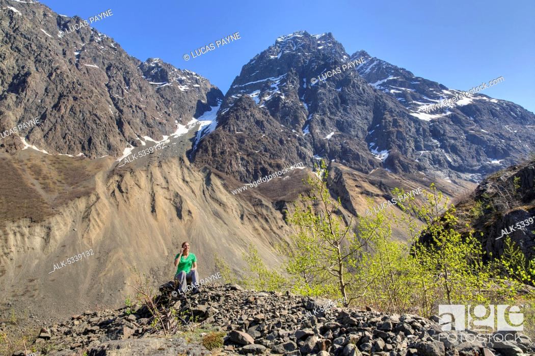 Imagen: Female hiker talking on a cell phone along the Eklutna Lake Trial and Chugach Mountains, Chugach State Park, Southcentral Alaska, Spring, HDR.