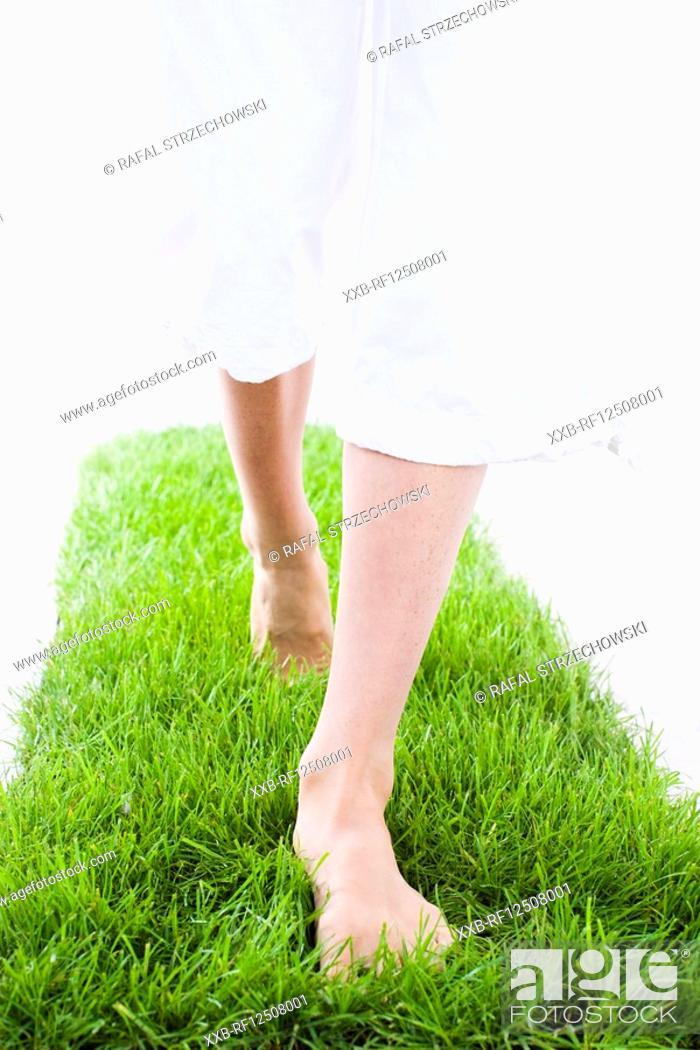 Stock Photo: woman walking on grass.