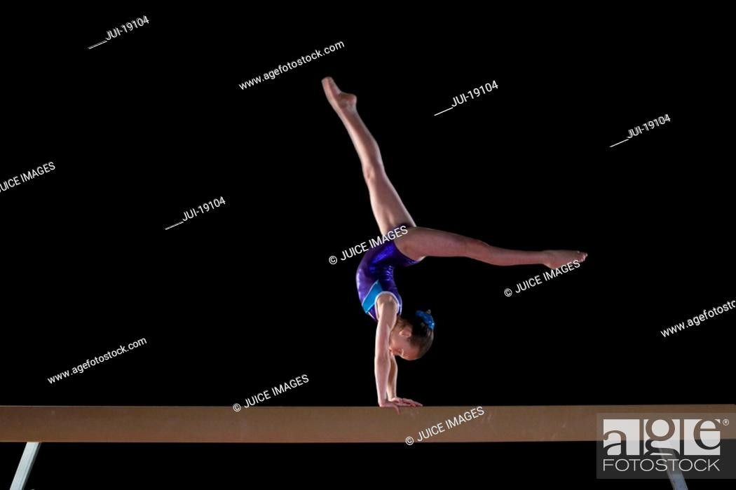 Stock Photo: Young female gymnast 9-11 performing handstand on balance beam, side view.