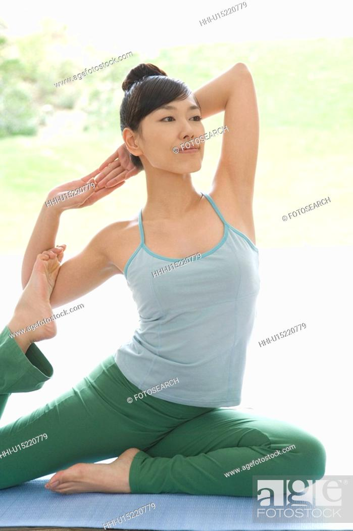 Stock Photo: Young woman doing yoga exercise, stretching, side view.