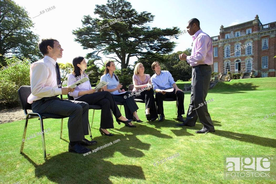 Stock Photo: Businessmen and women with folders in training course by manor house.