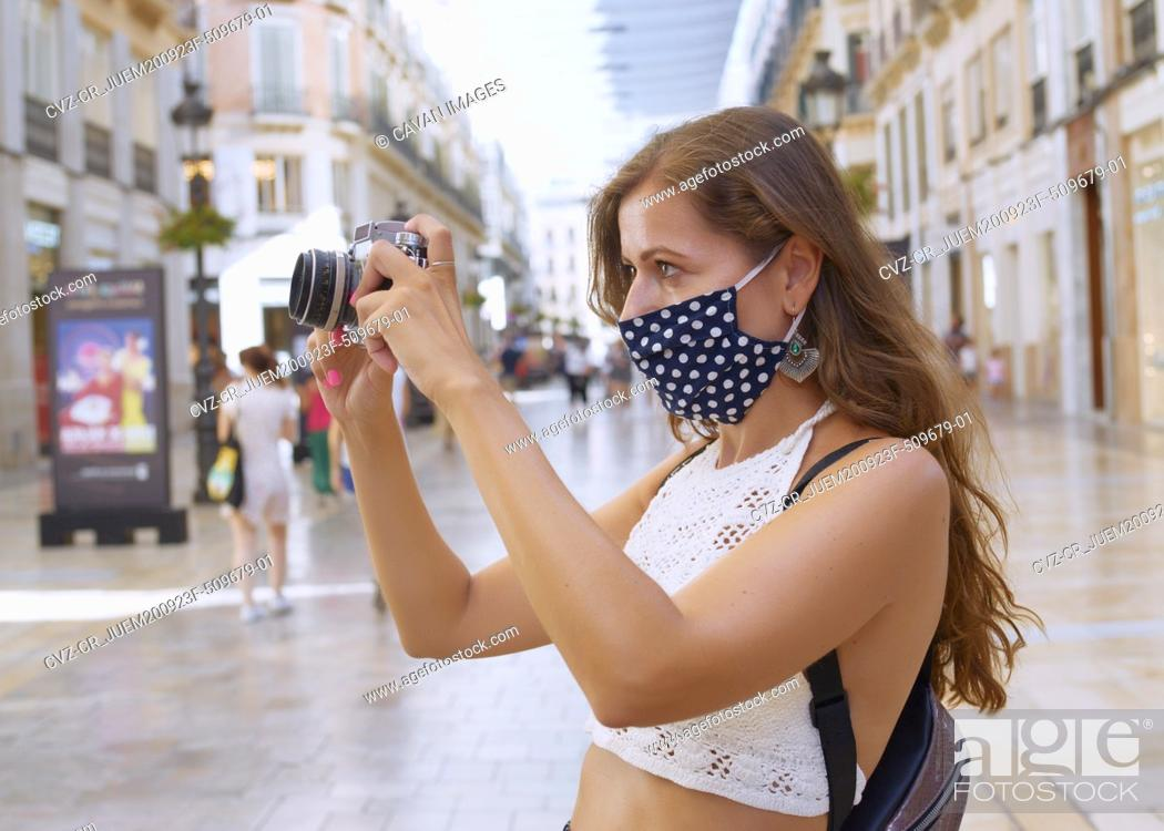 Photo de stock: Young tourist woman photographs the city with her camera.