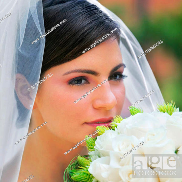 Stock Photo: Close-up of a bride smelling a bouquet of flowers.