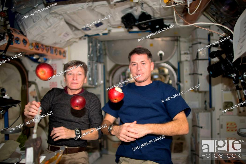 Stock Photo: Expedition 50 crew members Peggy Whitson (left) and Shane Kimbrough of NASA (right) share fresh fruit that was recently delivered by the HTV-6 cargo vehicle to.