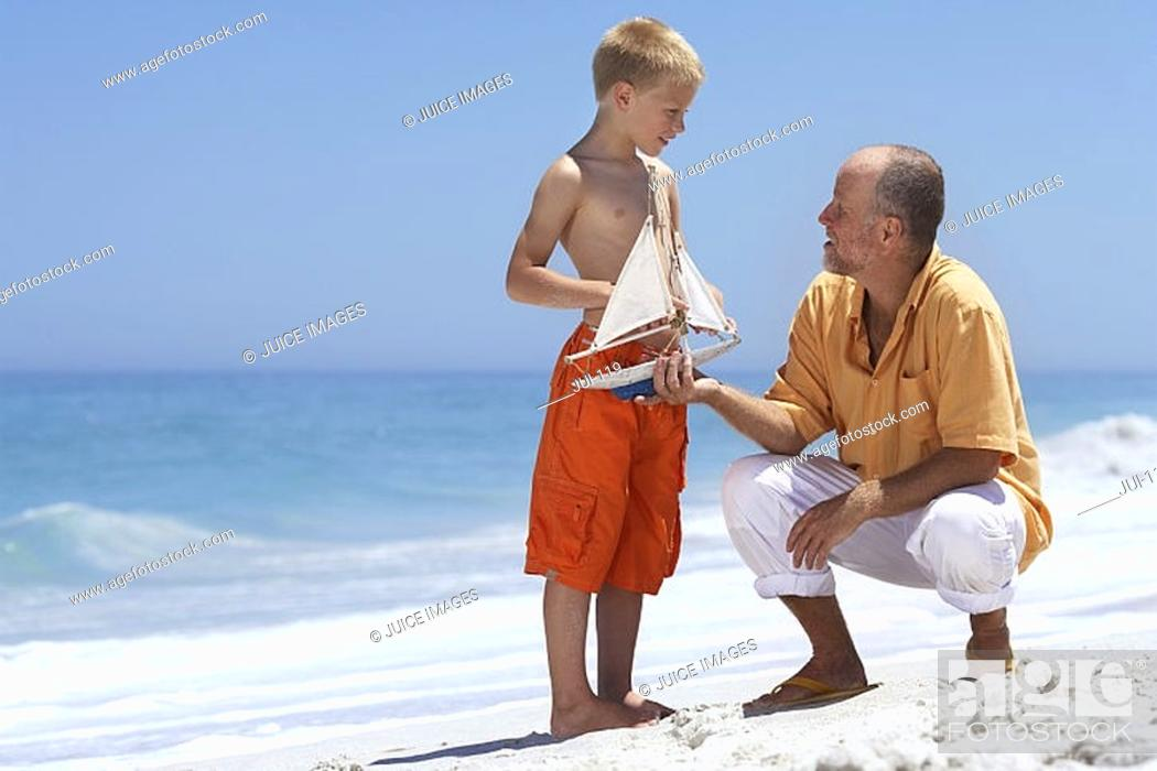 Stock Photo: Grandfather and grandson 7-9 playing with toy boat on sandy beach, smiling.