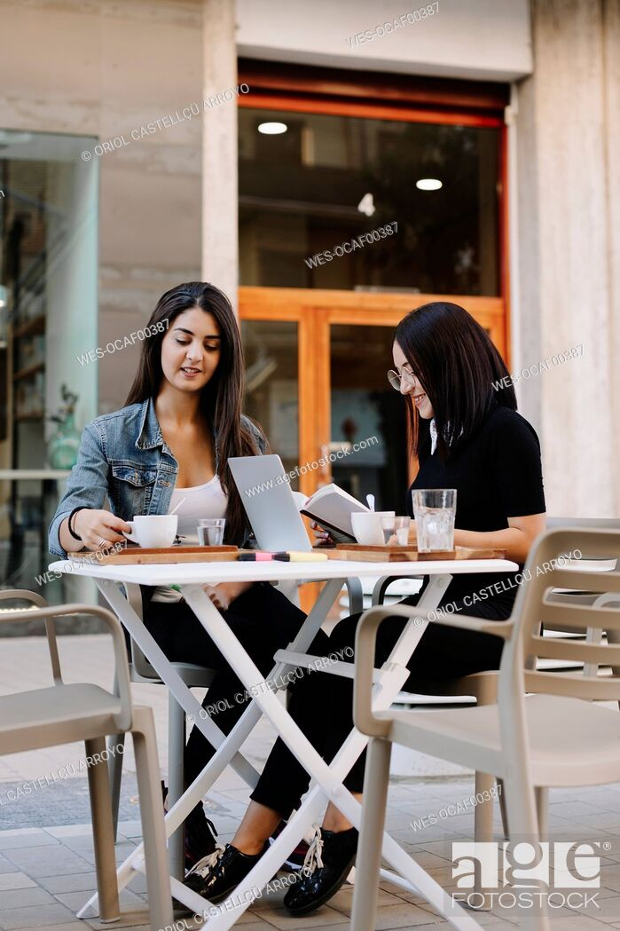 Stock Photo: Two friends sitting together at a pavement cafe with book and laptop.