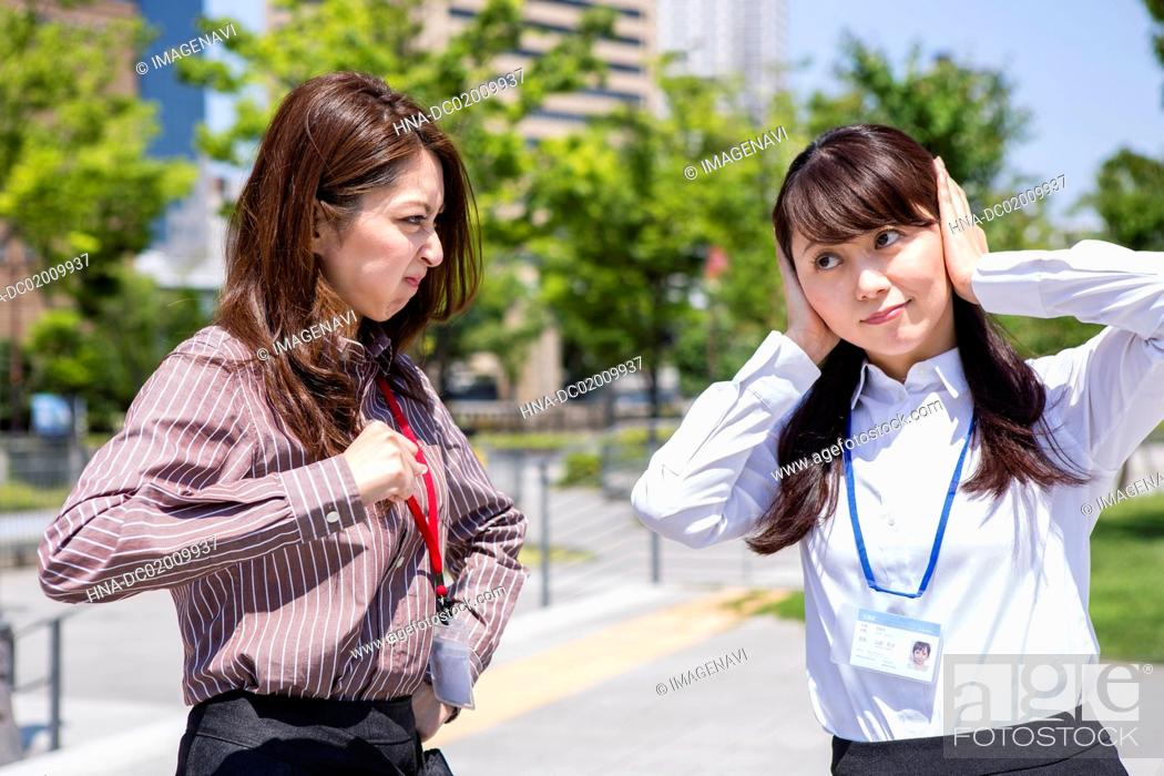 Stock Photo: A business woman being angry and the another woman covering her ears.