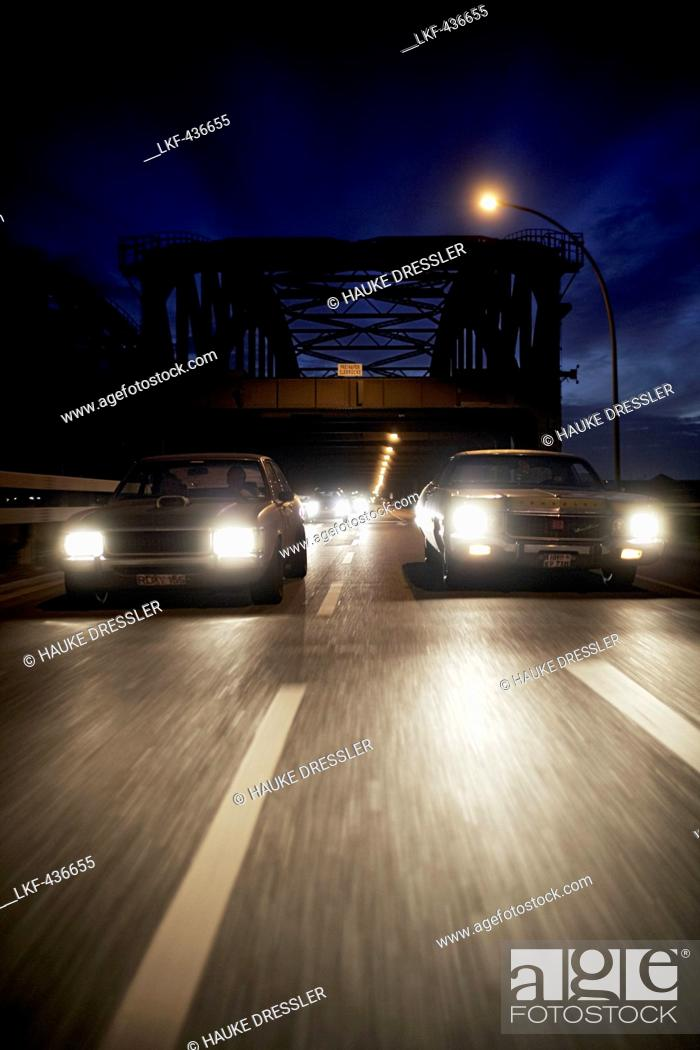 Stock Photo: Modern classic cars on the way at night, Motoraver group, Hamburg, Germany.
