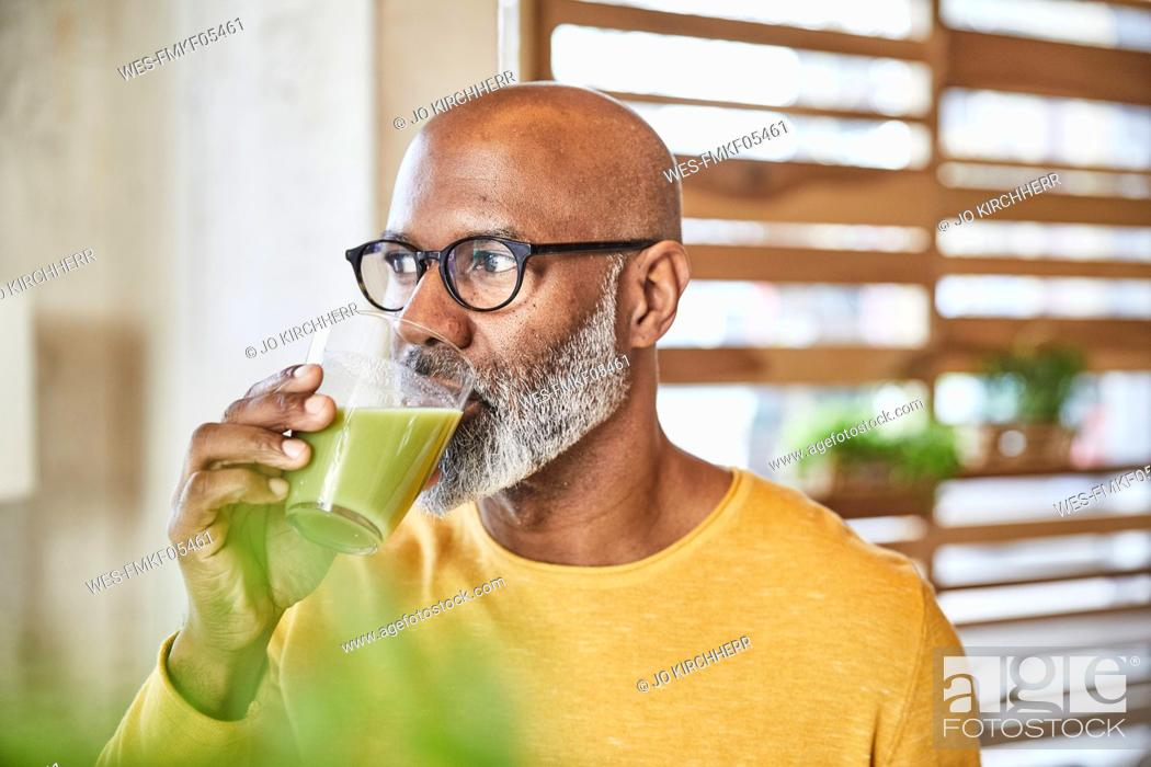 Stock Photo: Mature businessman in office drinking a smoothie.