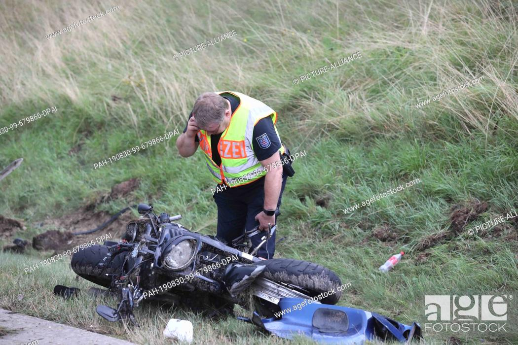 Stock Photo: 30 August 2019, Thuringia, Bad Lobenstein: At an accident site on the Autobahn 9, a policeman bends over a destroyed motorcycle at the edge of the road.