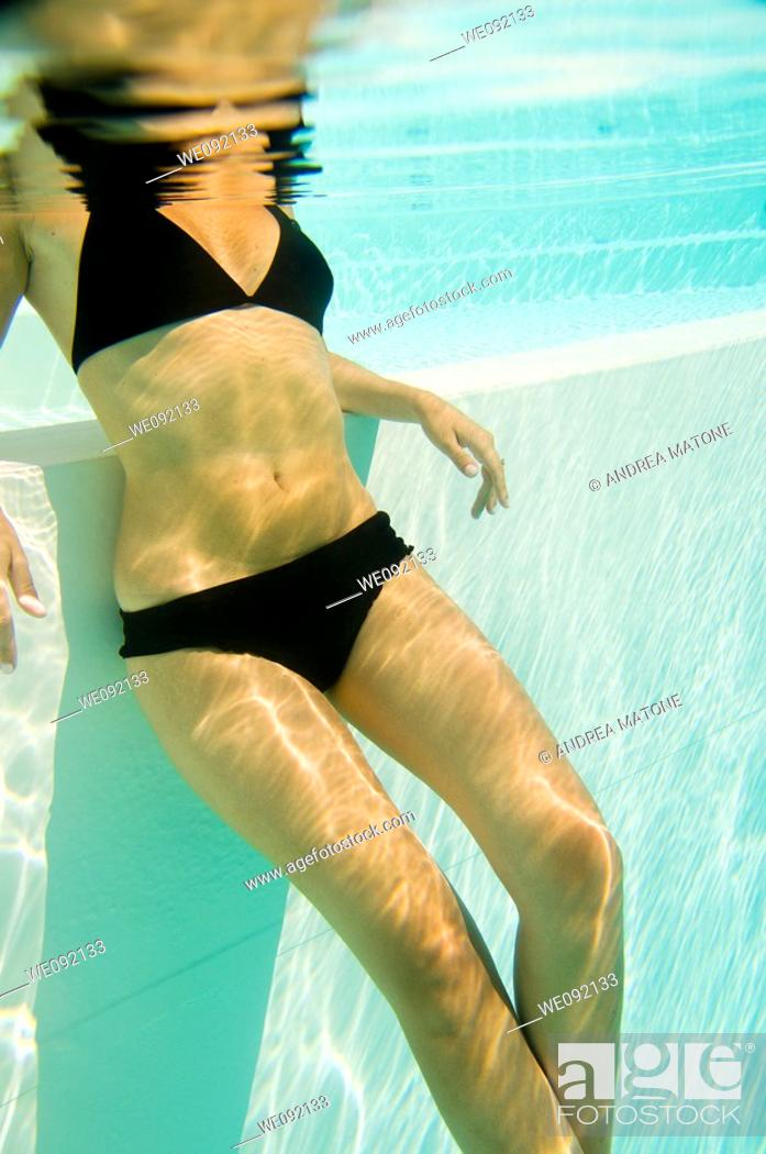 Stock Photo: Woman in bathing suit in a swimming pool seen from underwater.