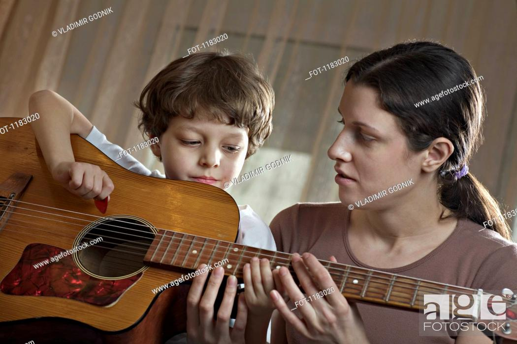 Stock Photo: A mother helping her young son with playing an acoustic guitar.