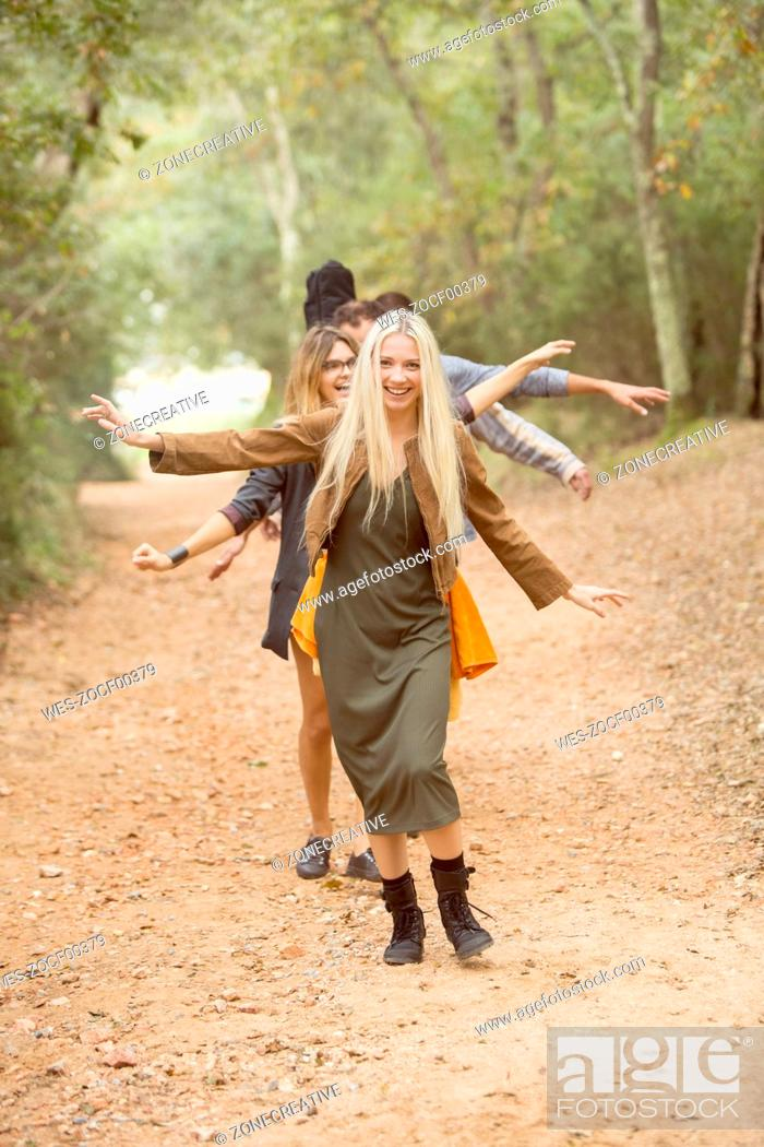 Stock Photo: Four happy friends having fun on path in the forest.