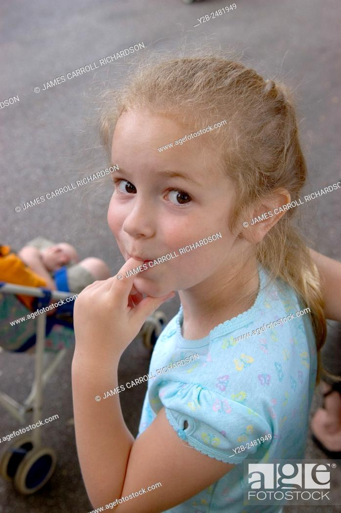 Stock Photo: Young girl looking coy with finger in her mouth.