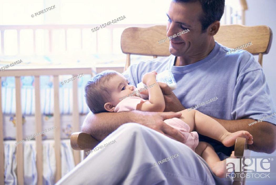 Stock Photo: Father feeding his baby boy.