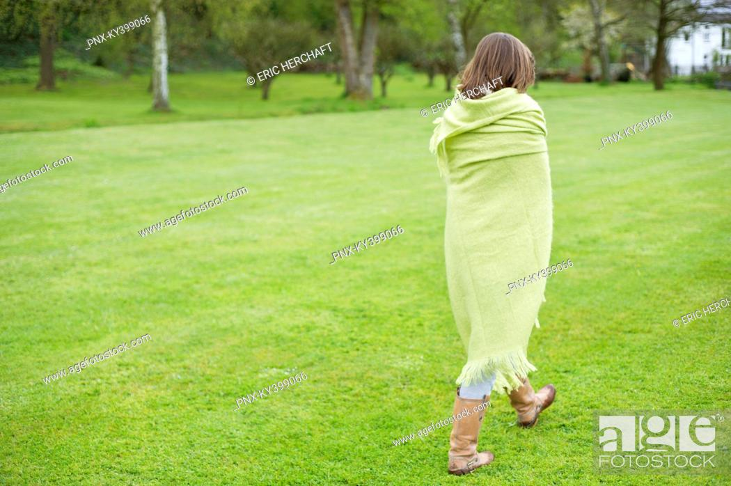Stock Photo: Girl wrapped in a blanket and walking in a field.
