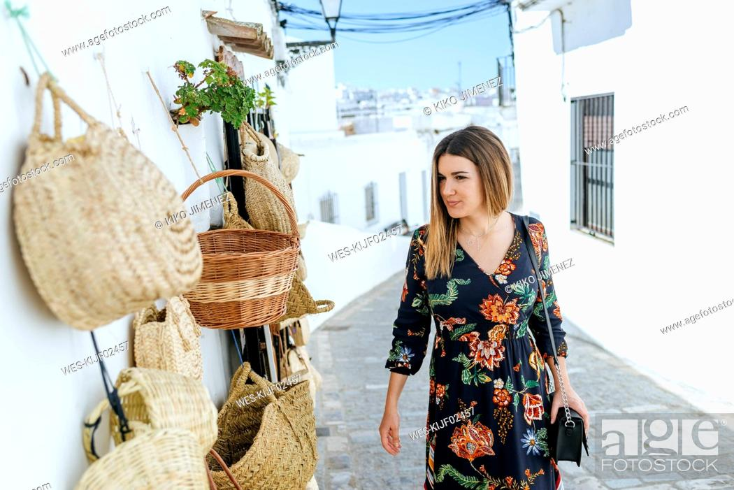 Stock Photo: Spain, Cadiz, Vejer de la Frontera, fashionable woman looking at bags and baskets at a shop.