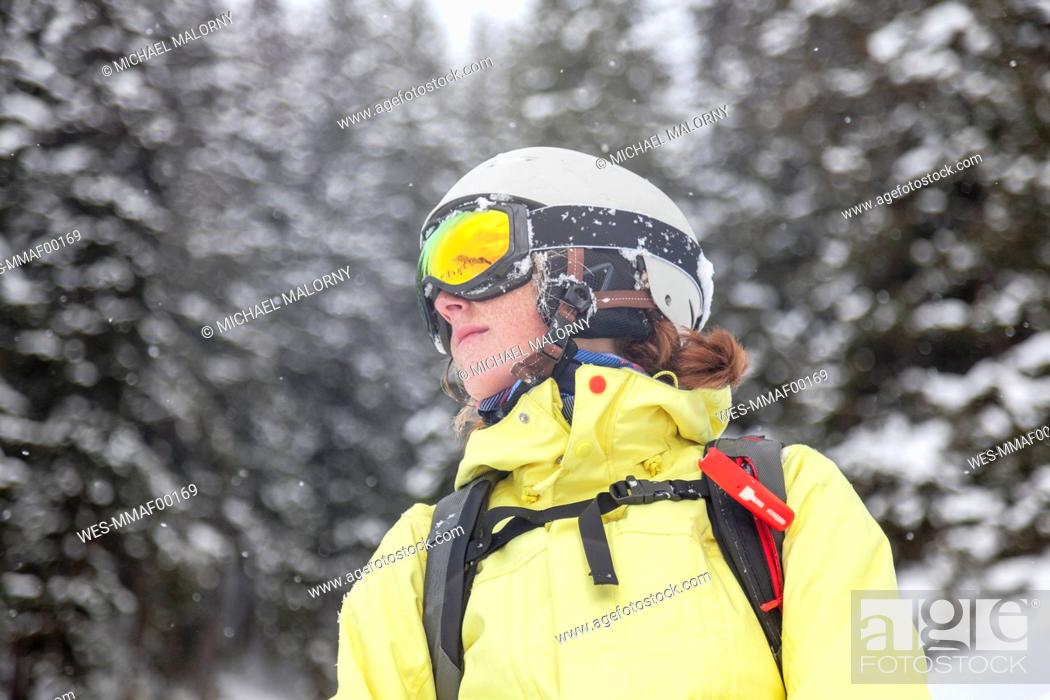 Stock Photo: Austria, Kitzbuehel, woman with ski helmet and avalanche backpack in snow.