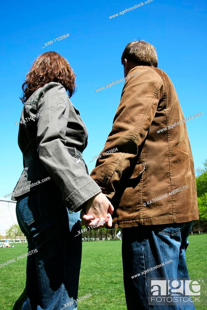 Imagen: Couple holding hands and looking away on a sunny day in a park.