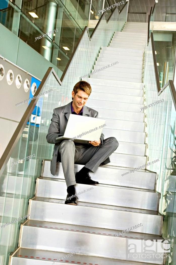 Stock Photo: Low angle view of a businessman sitting on a staircase and using a laptop.