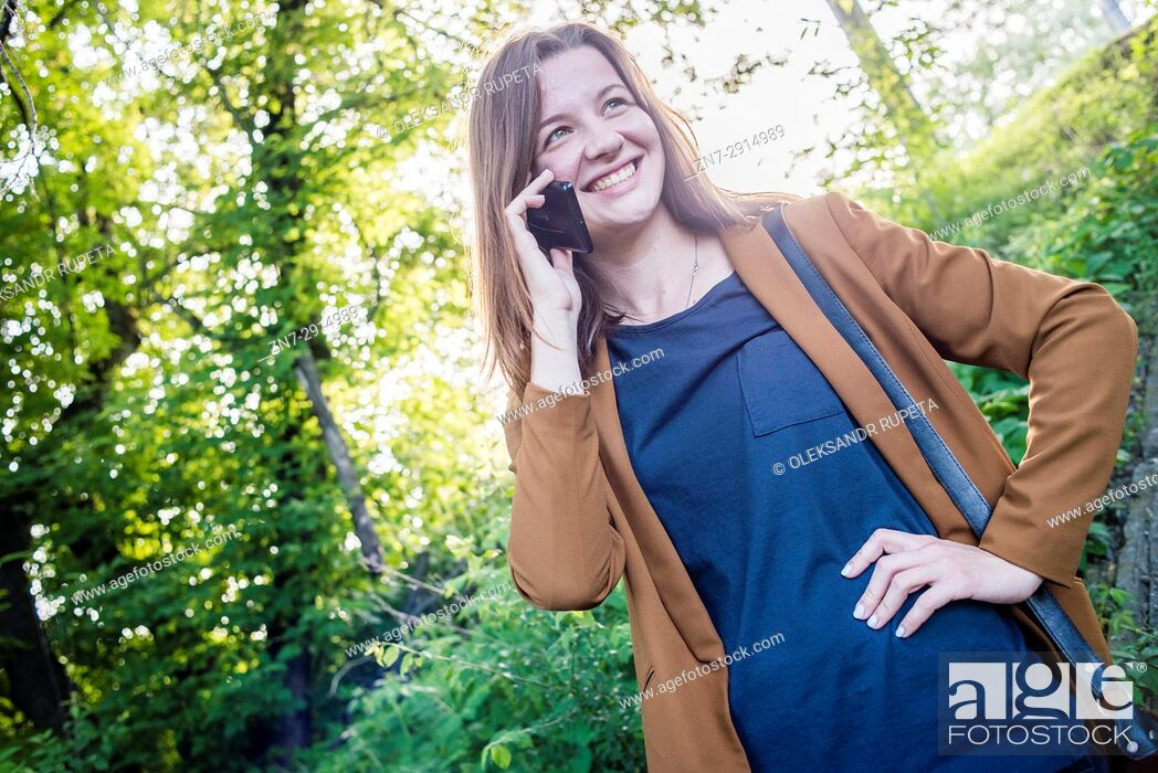 Stock Photo: A young woman talking on cell phone outdoors.