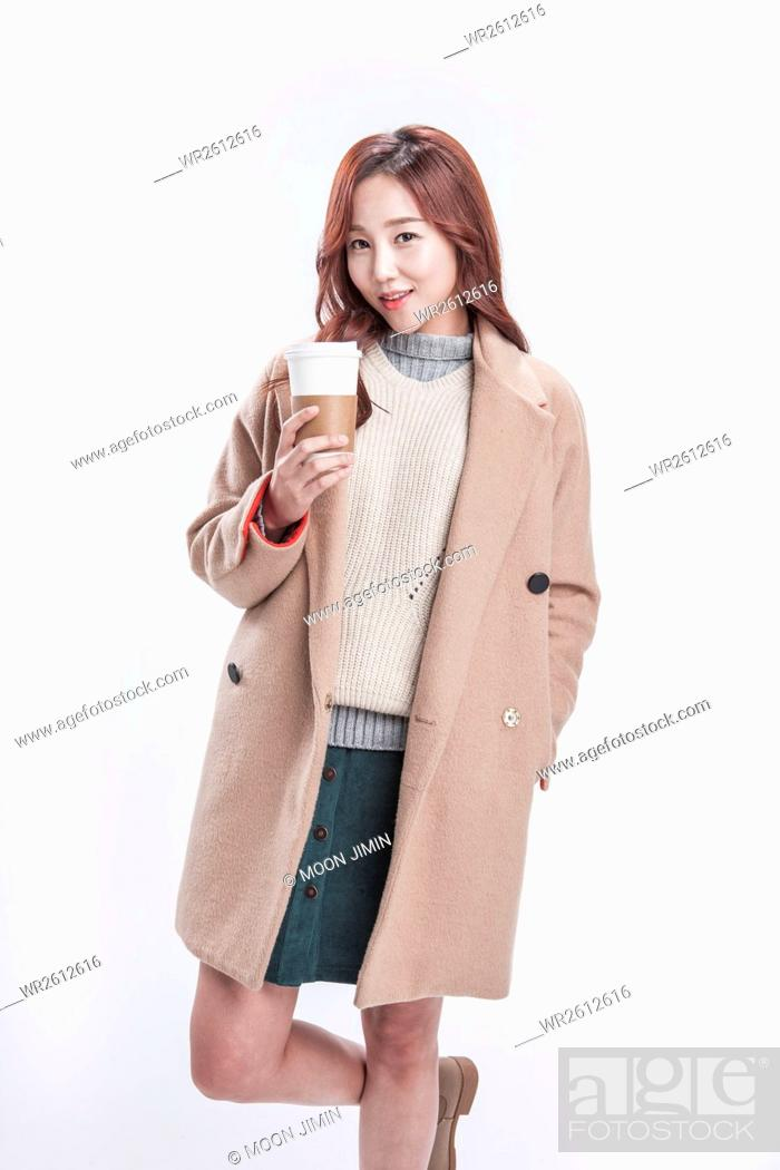 Imagen: Smiling woman in her early thirties in beige coat with takeout coffee.