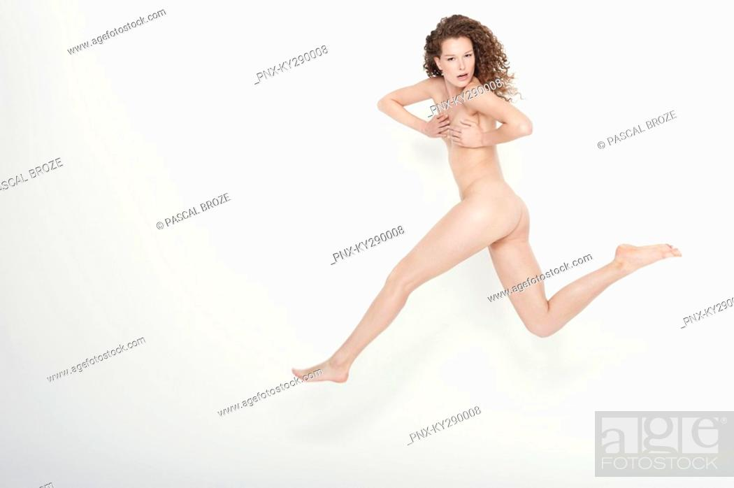 Stock Photo: Naked woman covering her breasts and jumping.