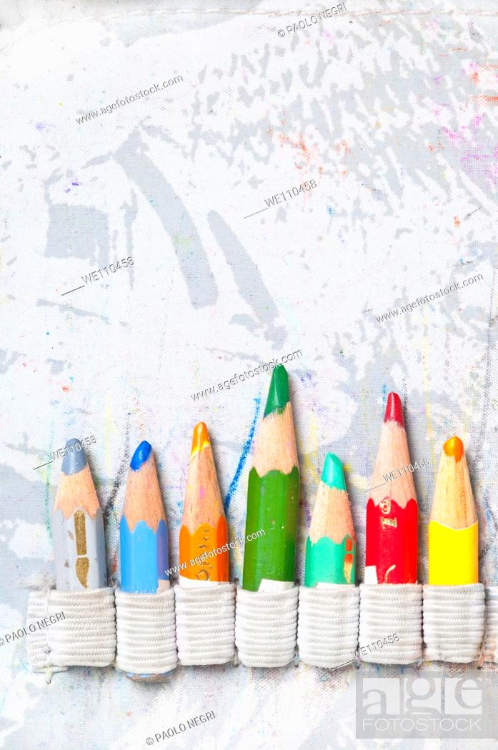 Stock Photo: seven pencils arranged side by side against gray background.