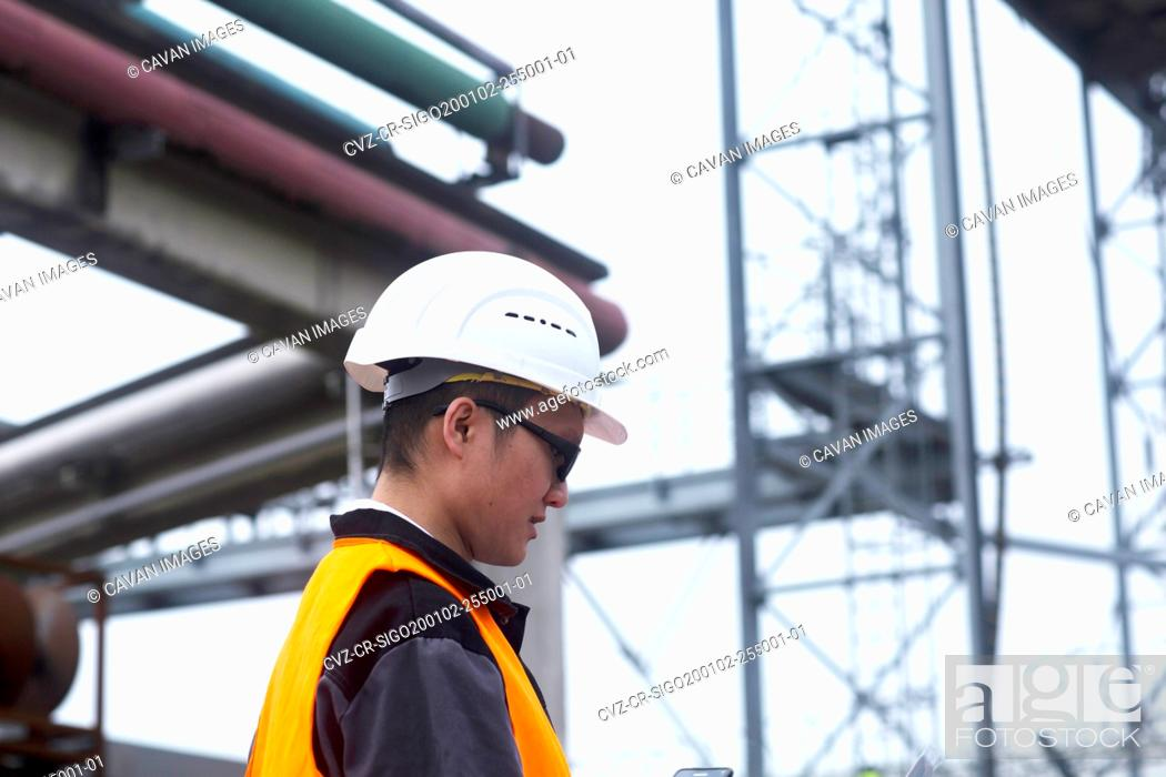 Imagen: worker outside in front of pipes.