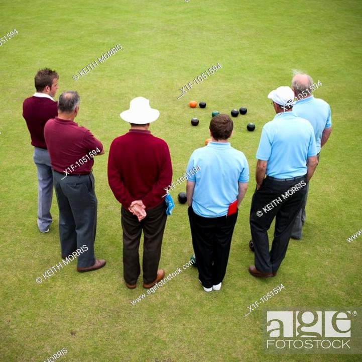 Stock Photo: Rear view of 6 men playing lawn bowls , Aberystwyth Wales UK.