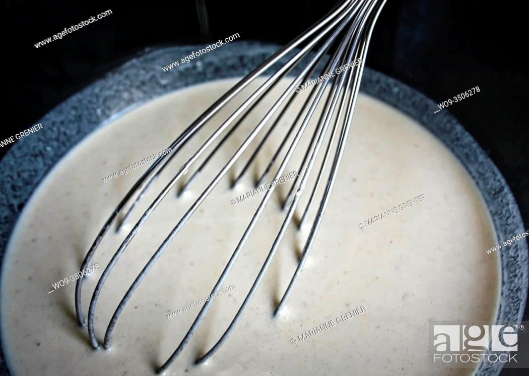 Stock Photo: Metal whisk in a white liquid dough close up.