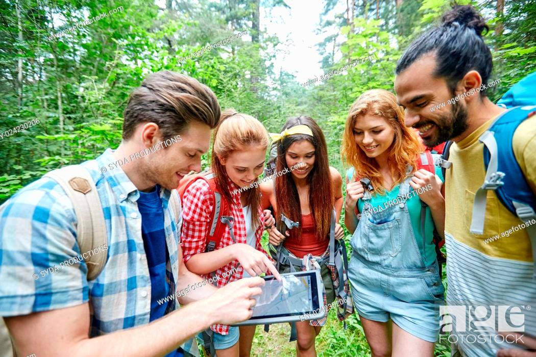 Stock Photo: technology, travel, tourism, hike and people concept - group of smiling friends walking with backpacks and map on tablet pc computer screen looking for location.