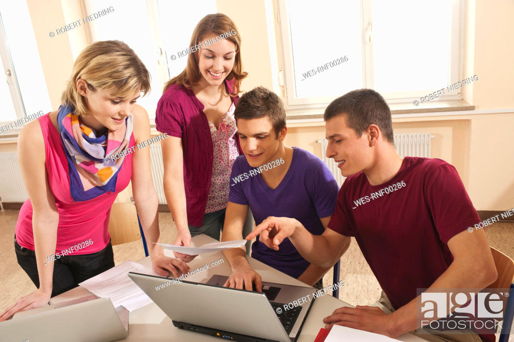 Stock Photo: Germany, Emmering, Students discussing and using laptop.