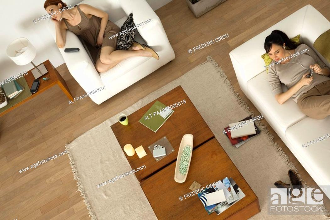 Stock Photo: Women relaxing in living room, one listening to MP3 player.