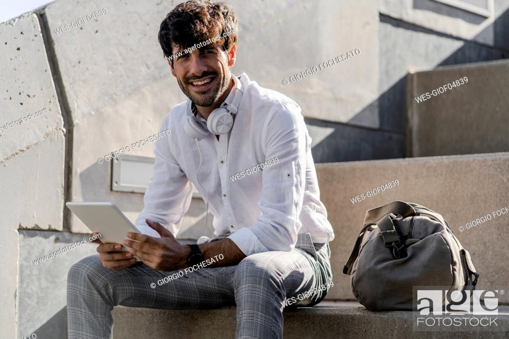 Stock Photo: Portrait of smiling young man sitting on stairs outdoors using tablet.