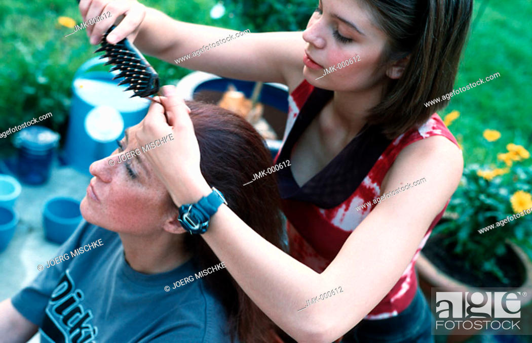 Stock Photo: A mother and daughter, a young girl and a woman in the garden on the terrace, dressing their hair.
