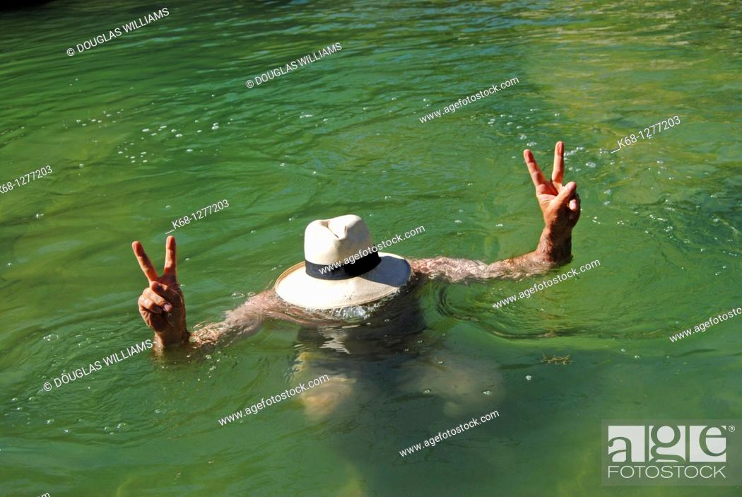 Stock Photo: Man wearing a panama hat in the water of a creek.