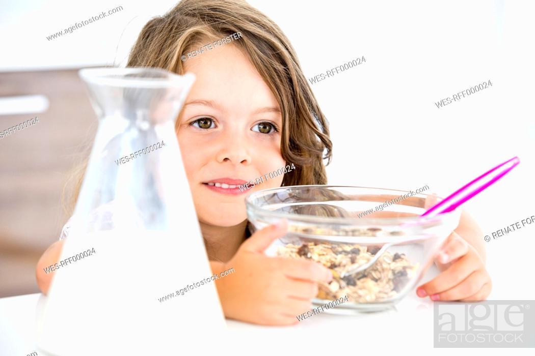Stock Photo: Germany, Girl eating muesli in kitchen.