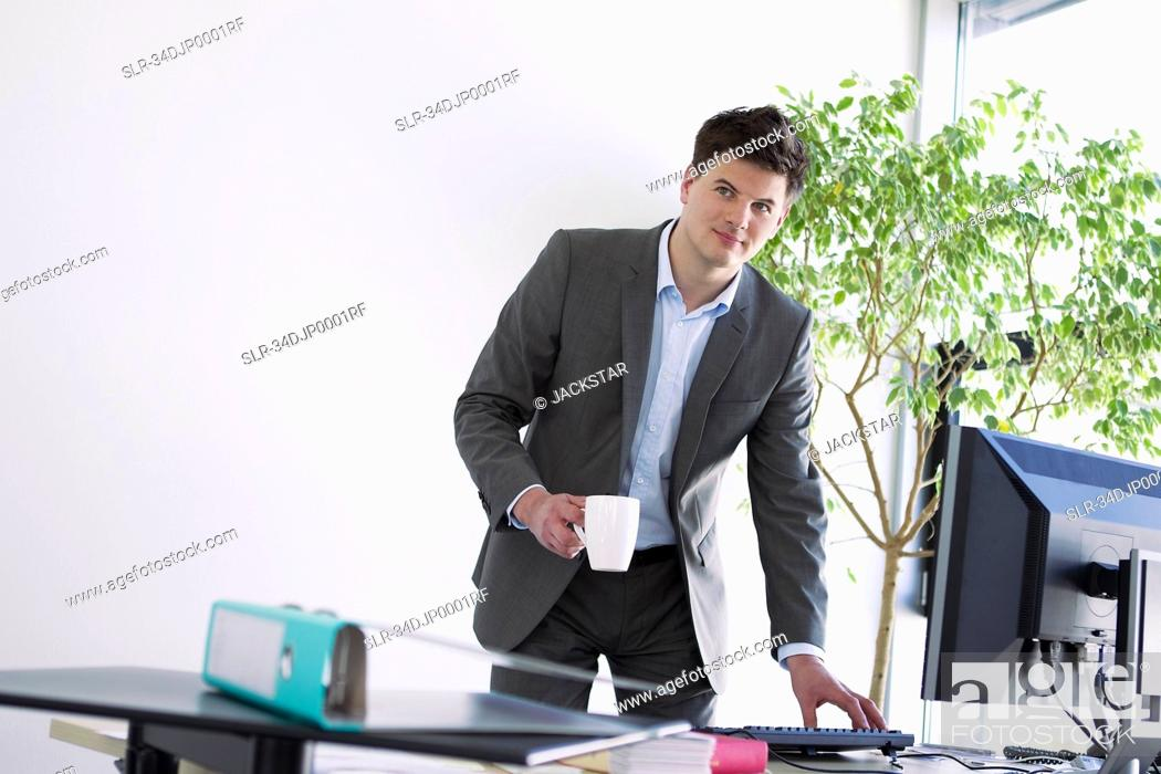 Stock Photo: Businessman with cup of coffee at desk.