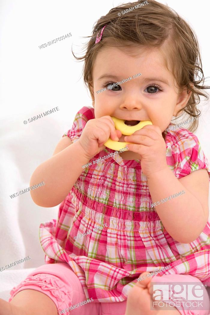 Stock Photo: Baby girl carrying dummy in mouth.