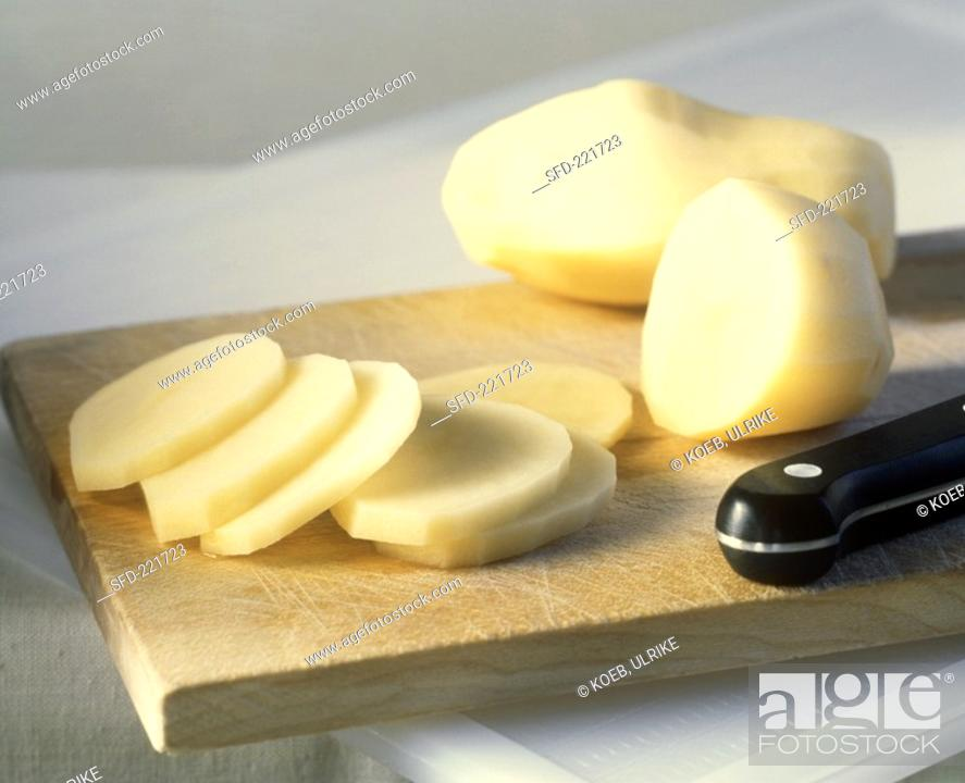 Stock Photo: Raw potatoes, peeled and some chopped.
