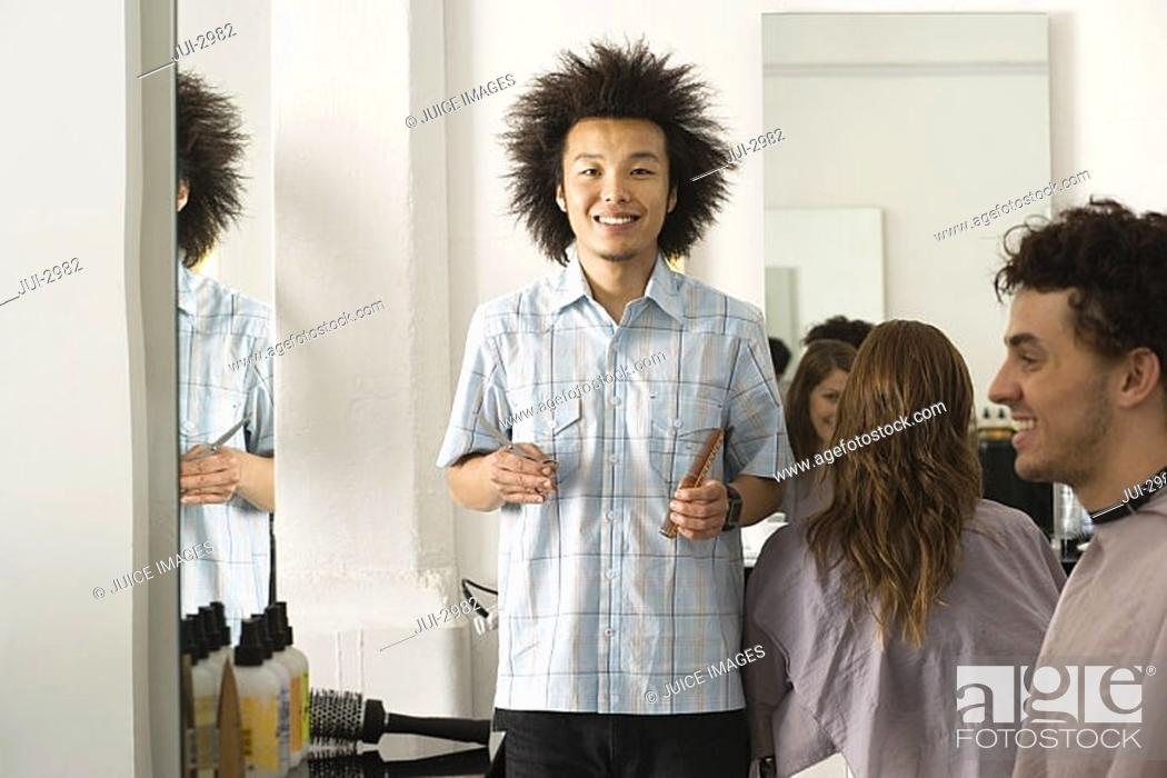Stock Photo: Customers sitting in hair salon, focus on hairdresser holding comb and scissors, smiling portrait.