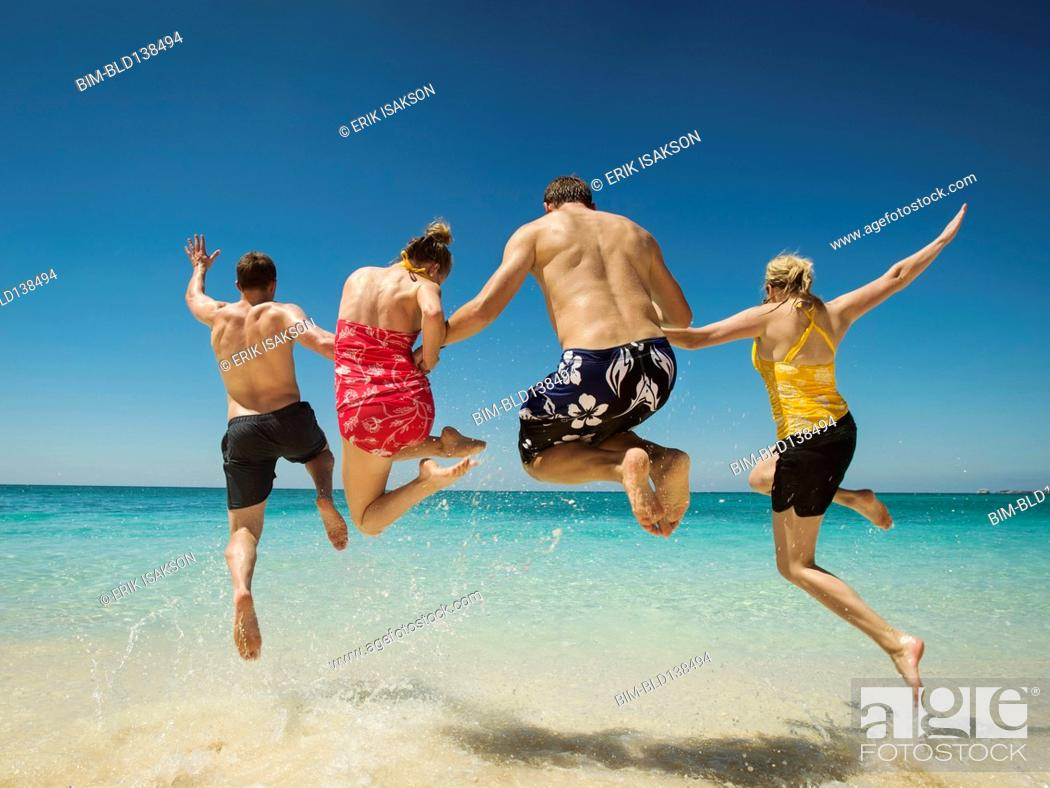 Stock Photo: Caucasian couples jumping for joy in water on tropical beach.
