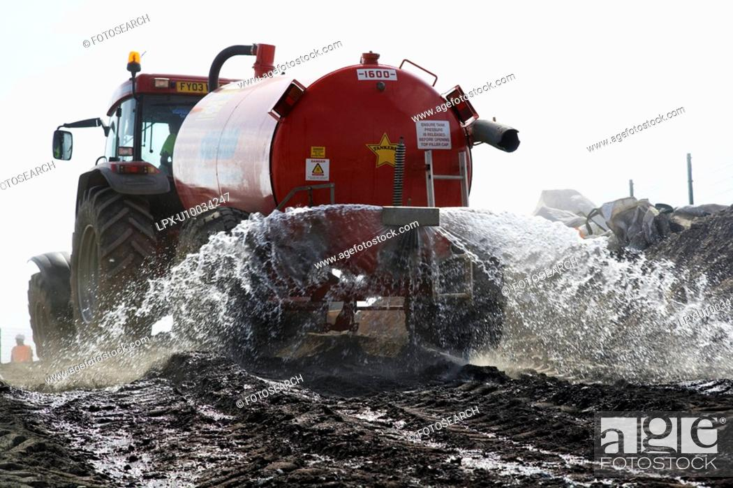 Stock Photo: Road building operations. Tractor speading water.