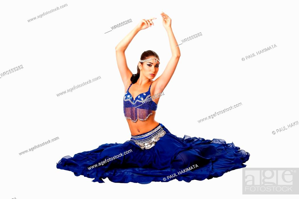 Imagen: Beautiful Israeli Egyptian Lebanese Middle Eastern belly dancer performer in blue skirt and bra with arms in air sitting, isolated.