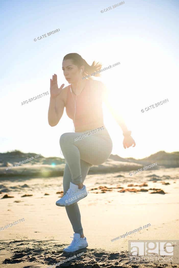 Imagen: Woman in her twenties working out during an early morning on the beach in Newport, Rhode Island.