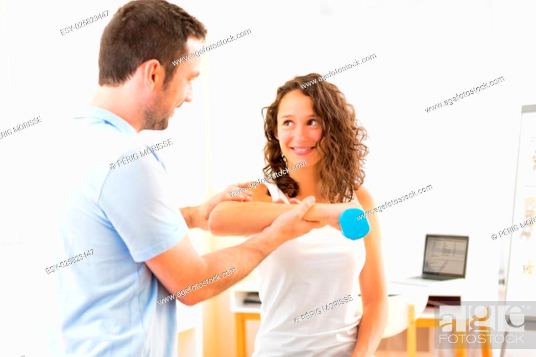 Stock Photo: View of a Young attractive woman doing exercise with physiotherapist.