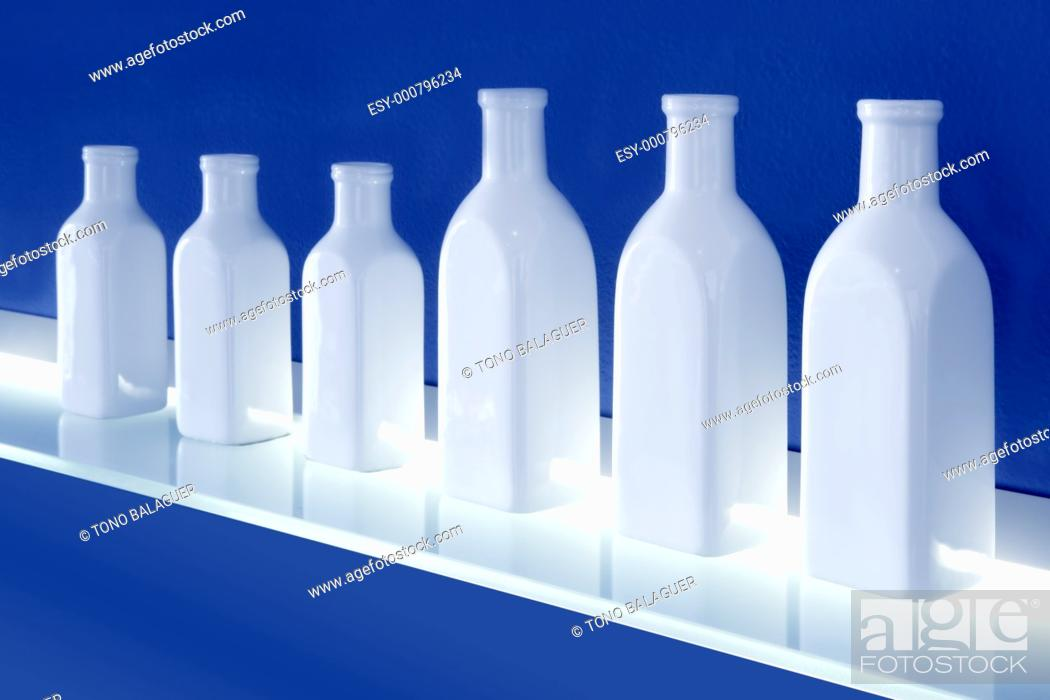 Stock Photo: white bottles in row blue background glowing shelf decoration.